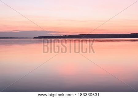 Scenic background in pink tones with a city on the horizon a river clouds and reflections on a smooth water surface at sunset