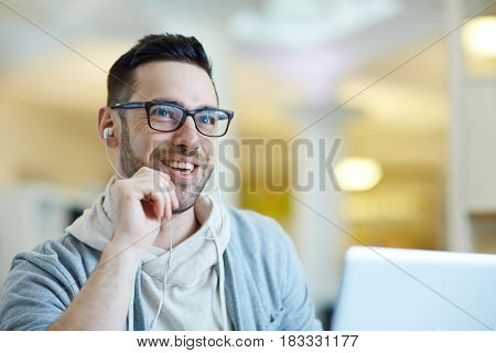 Portrait of contemporary adult man smiling while using laptop to video call somebody