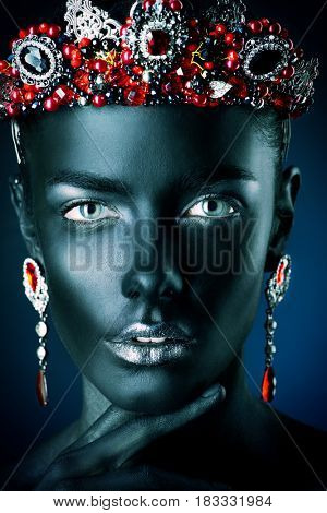 Jewelry industry. Fashion portrait of a beautiful young woman with perfect black skin wearing diadem with rubies and other precious stones. Jewelry and bijouterie. Body painting project.