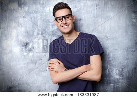 Portrait of a positive smiling young man in glasses. Studio shot.