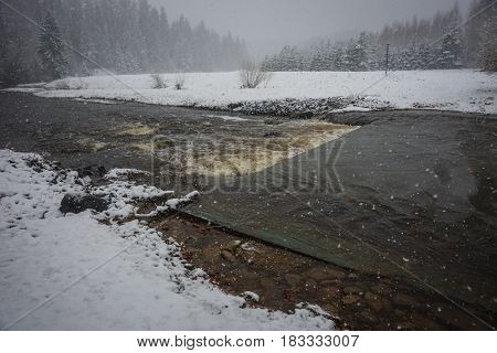 Scenic view of a river and its banks covered with fluffy snow during weather phenomena - snowfall in late April near Moscow