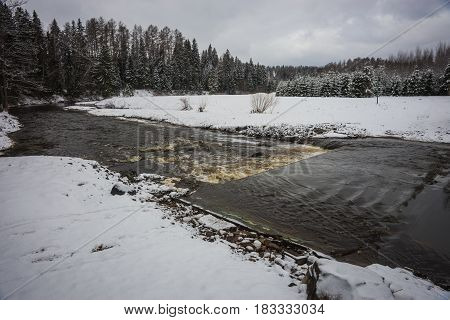 Scenic view of a river with its banks covered with fluffy snow during weather phenomena - snowfall in late April near Moscow