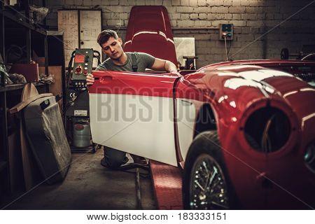 Mechanic working on car body details in restoration workshop