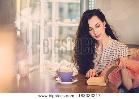 Beautiful lady reading novel in a cafe