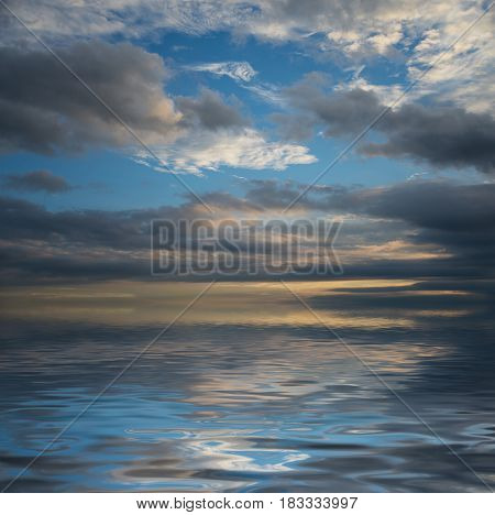 Beautiful seascape with dramatic sunset sky with dark clouds reflected in a water surface with small waves