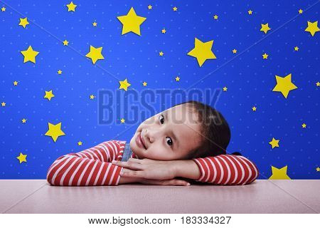Smiling Asian Child Resting On Desk