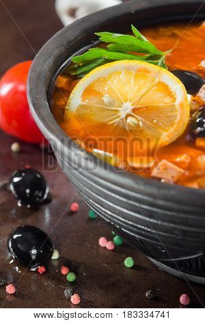Traditional Russian soup solyanka closeup in a bowl on the table.