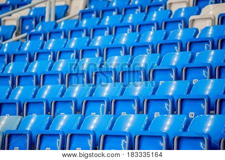 Rows of bright blue and white seats at stadium