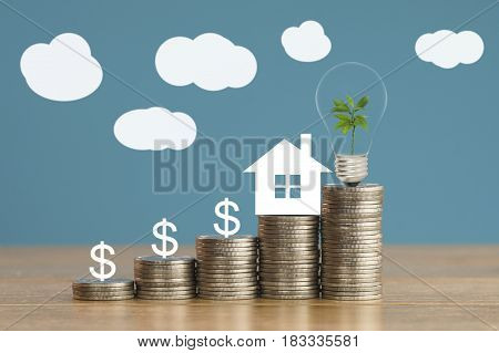 pile of coins and house paper with green small tree light bulb on money concept in save finance and grow of business about home