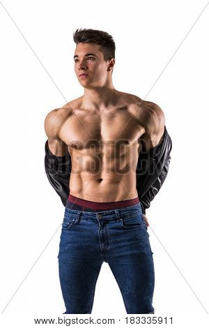 Handsome young muscular man shirtless wearing jeans, taking off leather jacket on naked muscle torso, isolated on white background in studio shot