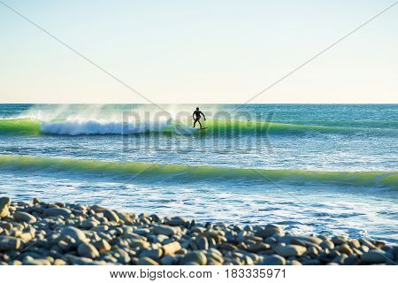 Surfing in the spring. Waves and surfer in ocean