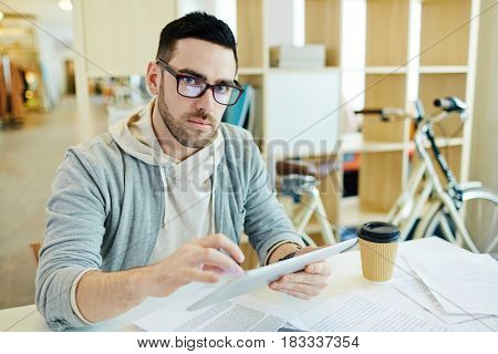 Portrait of confident handsome business man dressed in casual clothes working with tablet in creative office space and looking at camera