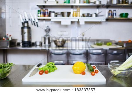 Fresh vegs and knife on table of restaurant kitchen
