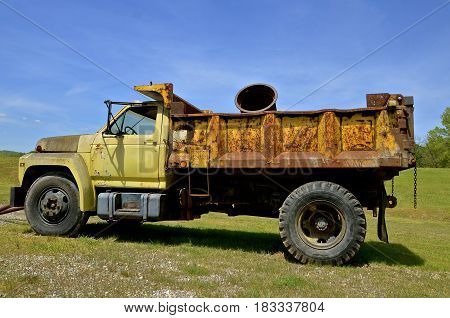 An old rusty truck used for hauling gravel and industrial supplies is parked on the grass