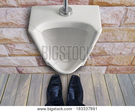 man standing infront of urinals to get pee or in toilet