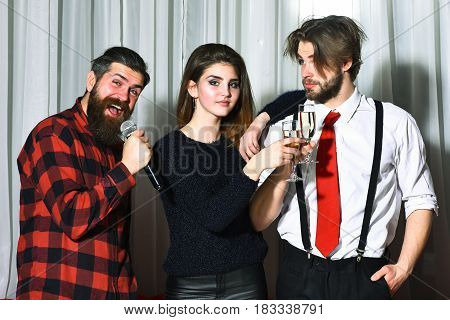 Happy friends celebrating at karaoke party on white curtain. Pretty girl beautiful woman and bearded man in suit pants with suspenders clinking glasses. Hipster with beard in red plaid shirt singing