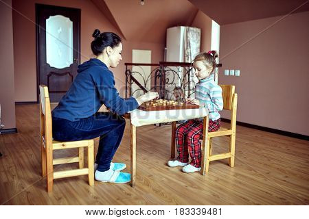 Mom and daughter playing draughts or checkers board game