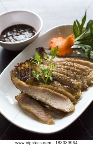 A dish of grilled pork neck served with Thai spicy sauce.