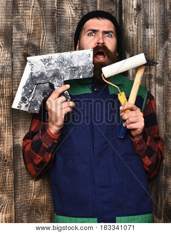 Bearded Builder Man Holding Various Building Tools With Surprised Face