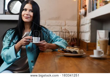 Girl with cup of coffee resting in cafe