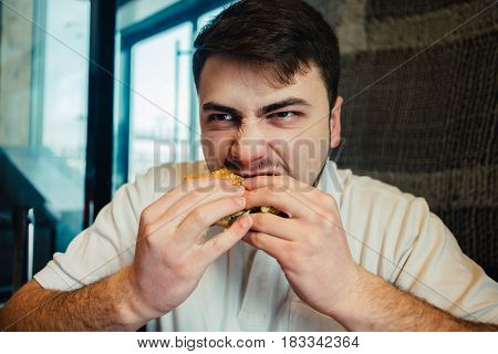 a young man in a white shirt eats greedily Burger