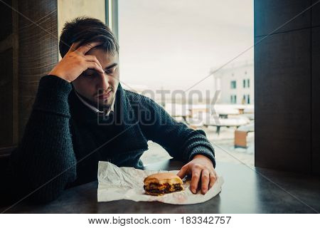 Portrait of a young bearded man in black sitting in the restaurant and fast food can no longer eat