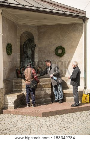 Altoetting,Germany-April 23,2017: People fill bottles with Holy Water from a fountain outside a church