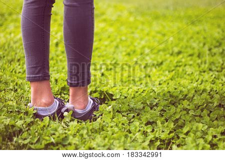 Young girl feet in sport shoes sneakers on green grass on meadow in spring. Lifestyle and fitness