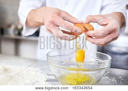 Chef breaking raw egg into bowl while preparing dough