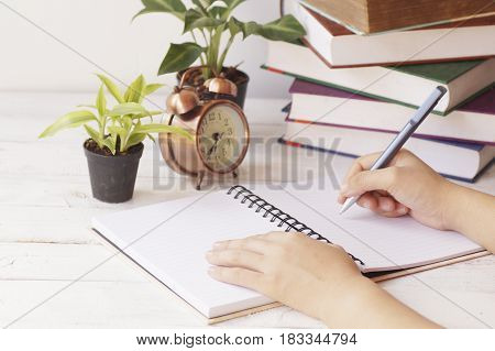 hand writing paper on desk and work place with clock book and palnt