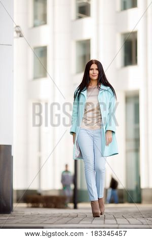 Beautiful woman walking down street against building background