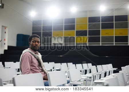 Serious student sitting on one of chairs in conference room