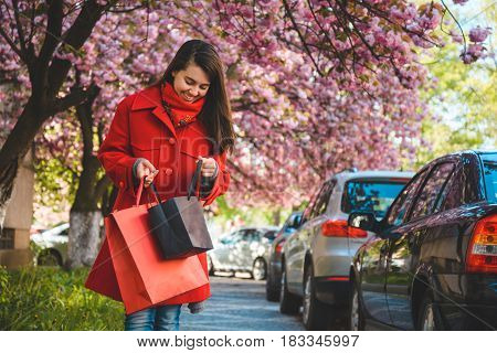 happy young women walking after shopping by street blooming with sakura looking in bags