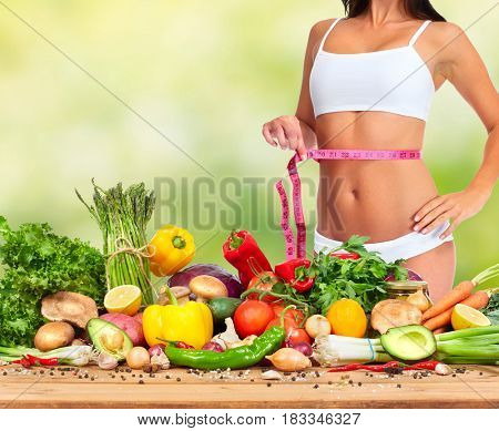 Woman waist with measuring tape over food background.
