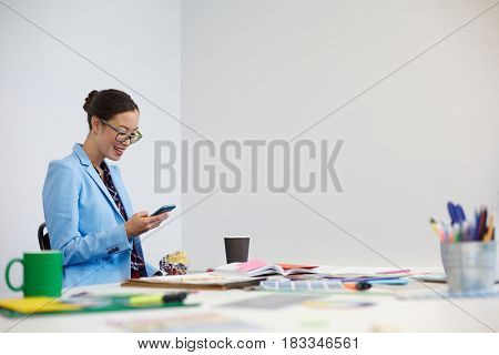 Pretty student of design faculty eating hamburger and reading sms in smartphone