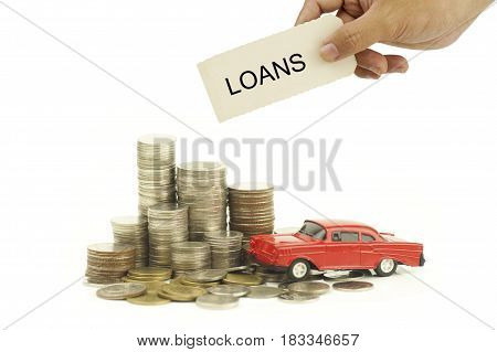 hand holding lons sign over money coins and toy car isolated on white background