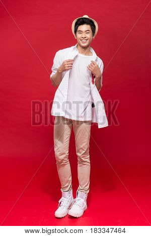 Full length of elegant young handsome asian man with hat. Cool fashion male model.