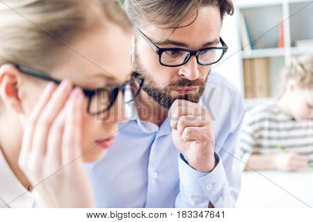 Concentrated Businesswoman And Businessman With Eyeglasses Working In Office, Little Girl Behind