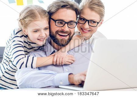 Happy Father, Mother And Daughter Hugging And Using Laptop In Office