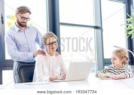 Smiling Businesswoman And Businessman With Eyeglasses Working With Laptop Daughter Drawing Near In O