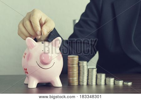 hand of businesswomen put money on pink of piggy bank and pile of coins concept in growth save and investment in business