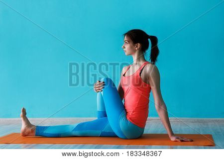 Young sportwoman engaged in gym on rug