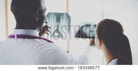 Doctors analyzing an x-ray in a metting.
