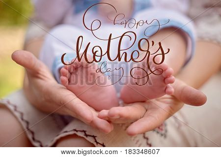 Mother hold the feet of her newborn son and Happy mothers day text. Calligraphy lettering hand draw.