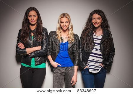 three happy women in leather jackets smiling to the camera in studio