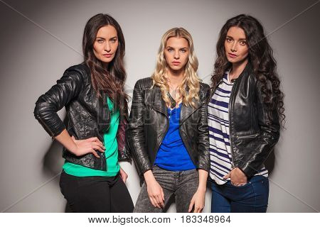 three young women fashion models posing together in studio