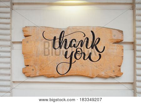 Blank wood board on wall and text Thank you. Calligraphy lettering hand draw.