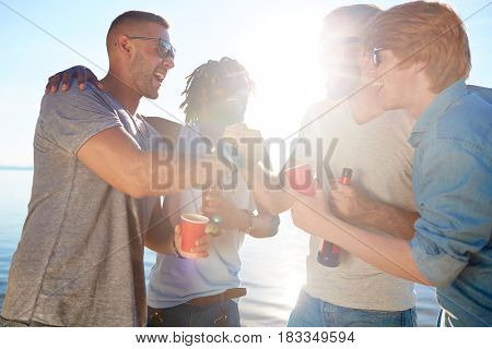 Ecstatic guys with drinks enjoying sunny day on the beach