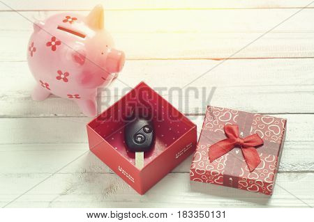 car key on a paper box with red ribbon bow on black natural wooden table background. Birthday's Day gift or present abstract concept.