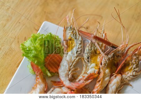 shrimps grilled served in plate on wood table